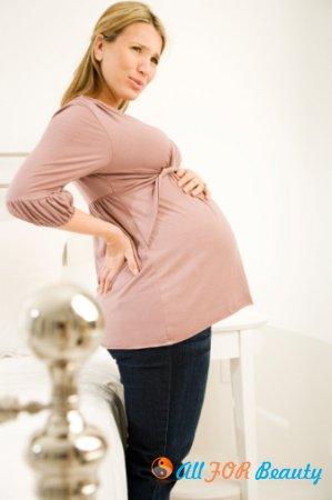 Почему болит поясница у беременных?